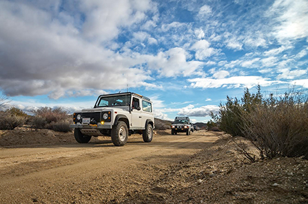 several high-clearance, four wheel drive vehicles caravan down the dirt Pinkham Canyon Road