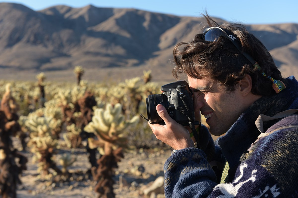 A young man holds a camera up to his eye as he directs it at the Cholla Cactus Garden