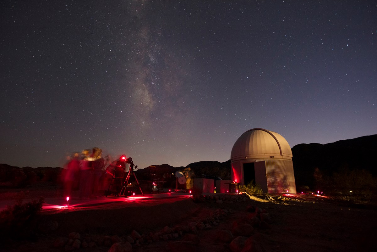 Color photo of people viewing the night sky through telescopes with the Milky Way in the sky.