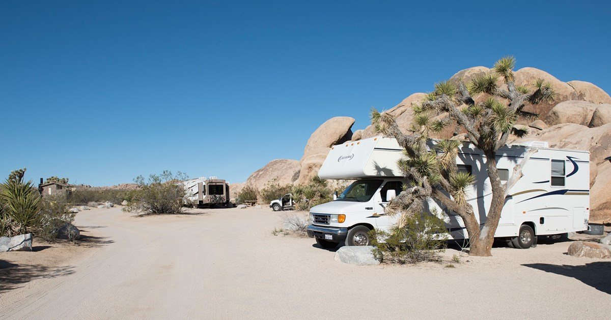 Color photo of RVs in sites at Belle Campground with rock formations and Joshua trees nearby. NPS / Hannah Schwalbe