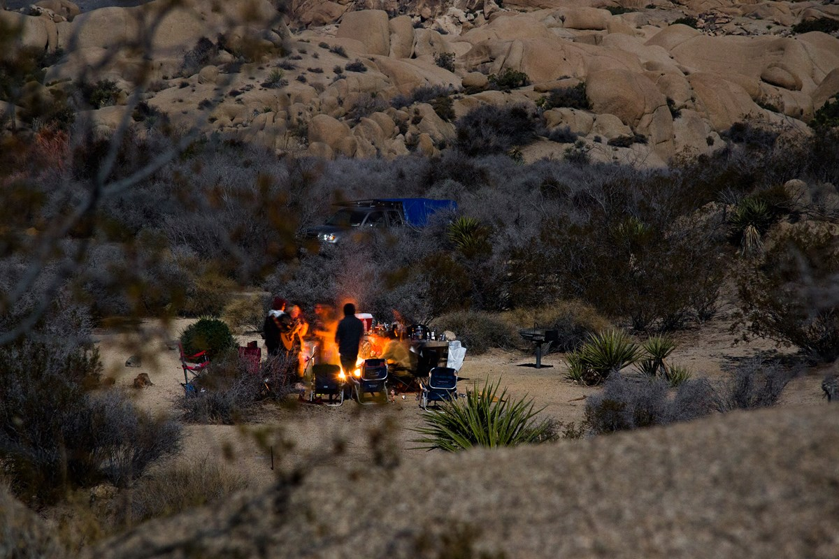 Color photo of people standing around a campfire with a guitar. NPS / Brad Sutton