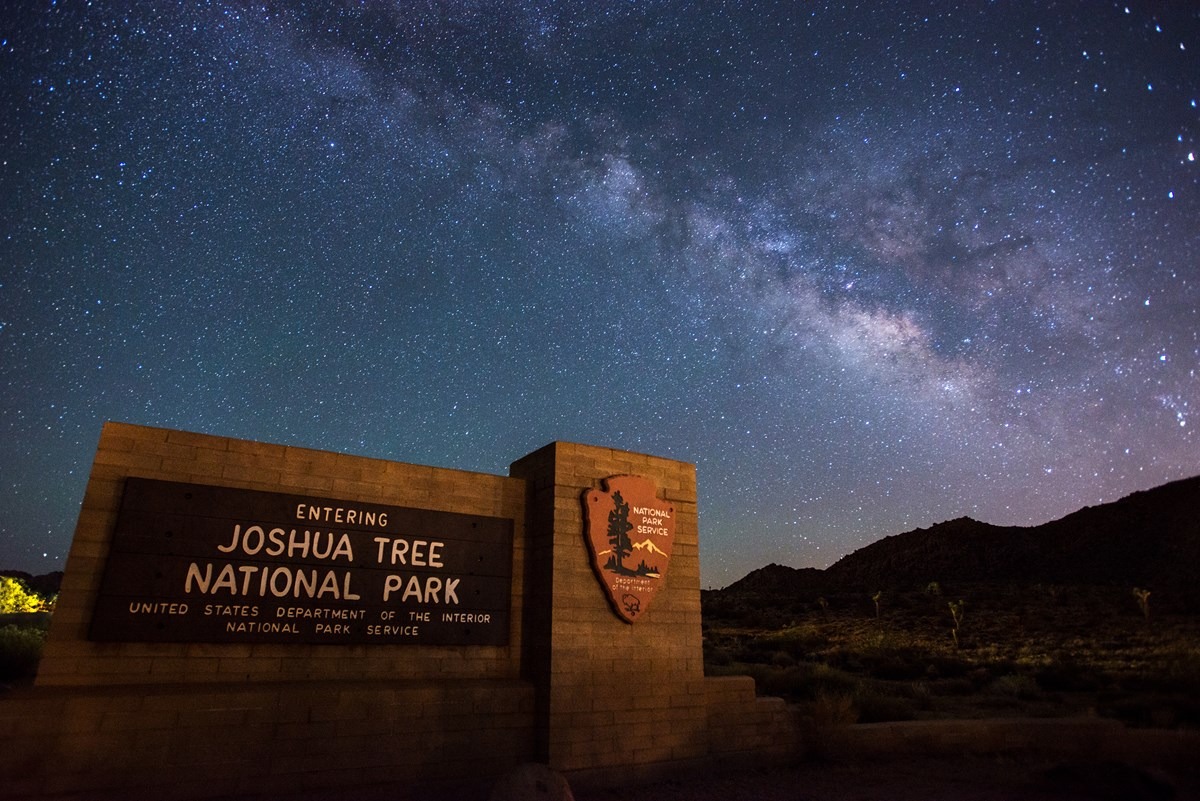 Color photo of brilliant milky way in the sky and the park entrance sign in the front.