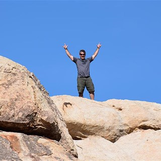 A man standing on top of rocks with his arms stretched up into the air.