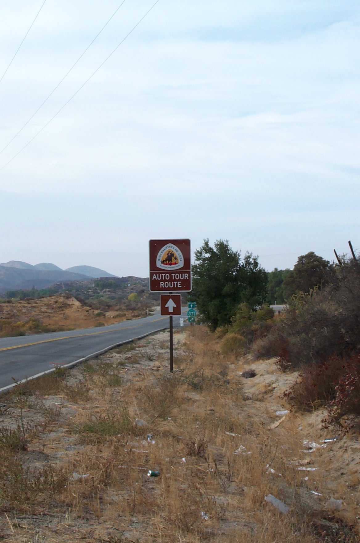 An Anza Trail Auto Route sign along a highway with mountains in the background.