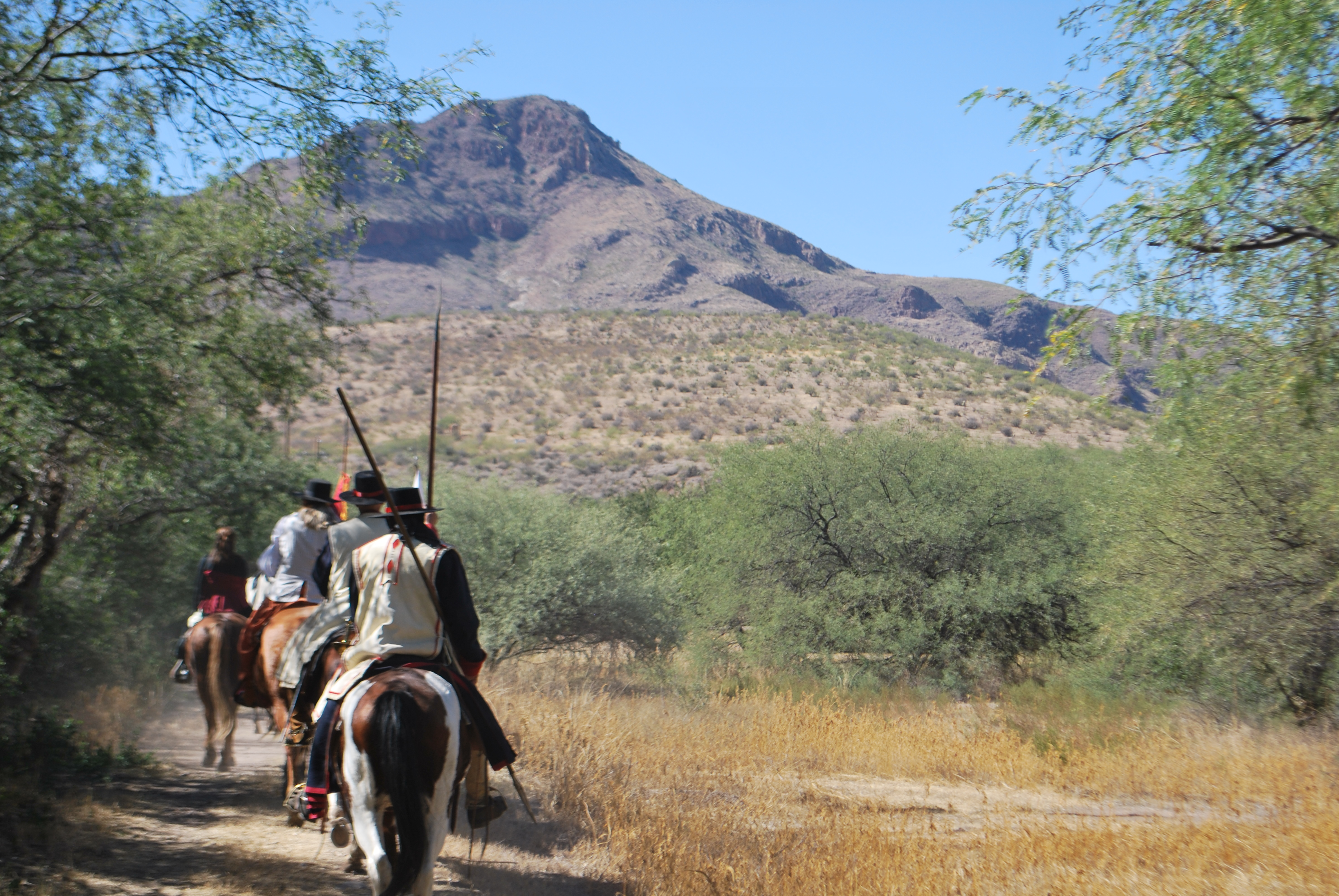 Living History - Mounted colonial Spanish soldiers ride the Anza Trail in a riparian desert landscape towards a mountain.