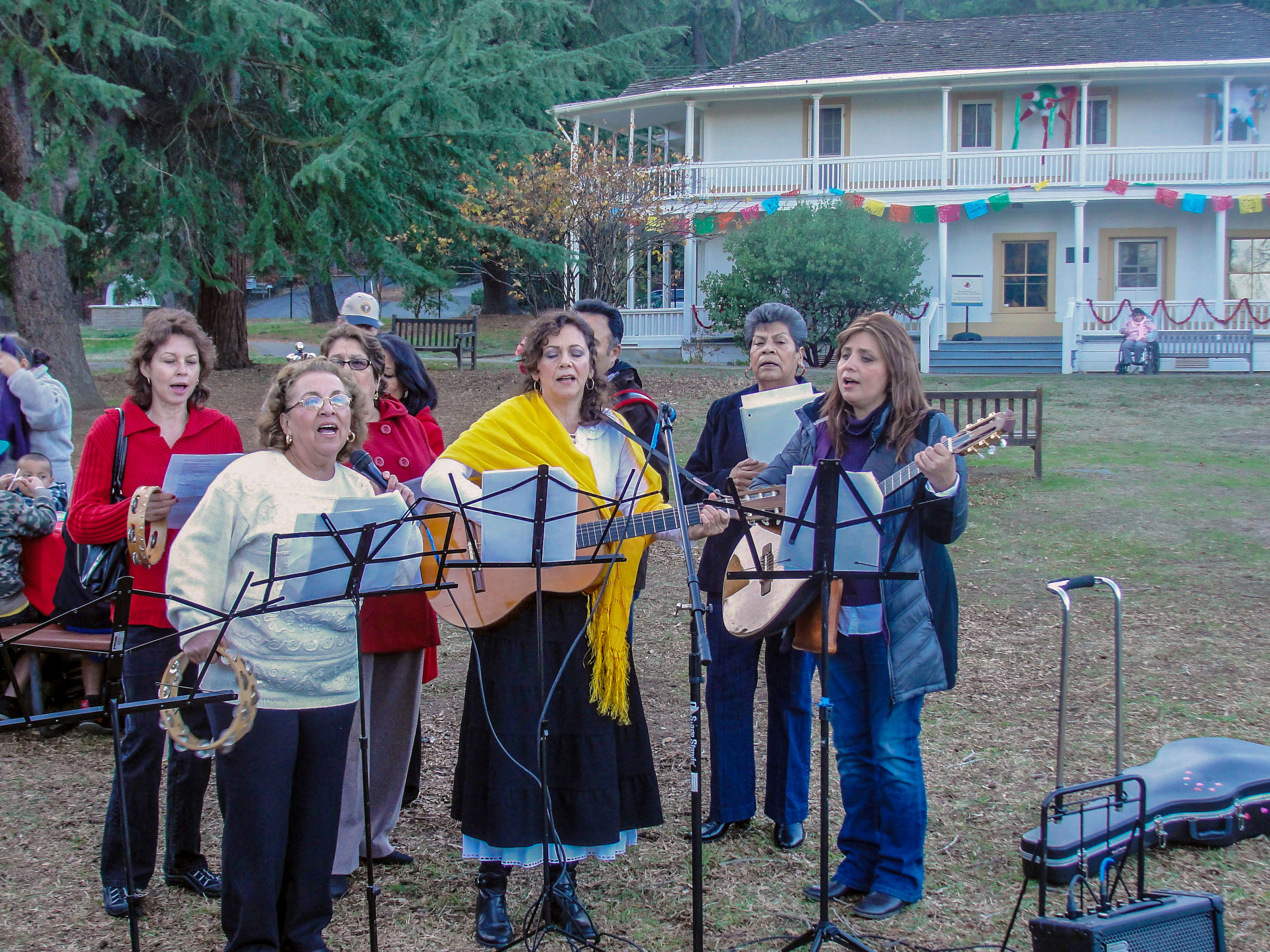 A festive choir sings and plays music outside a whitewashed decorated adobe.