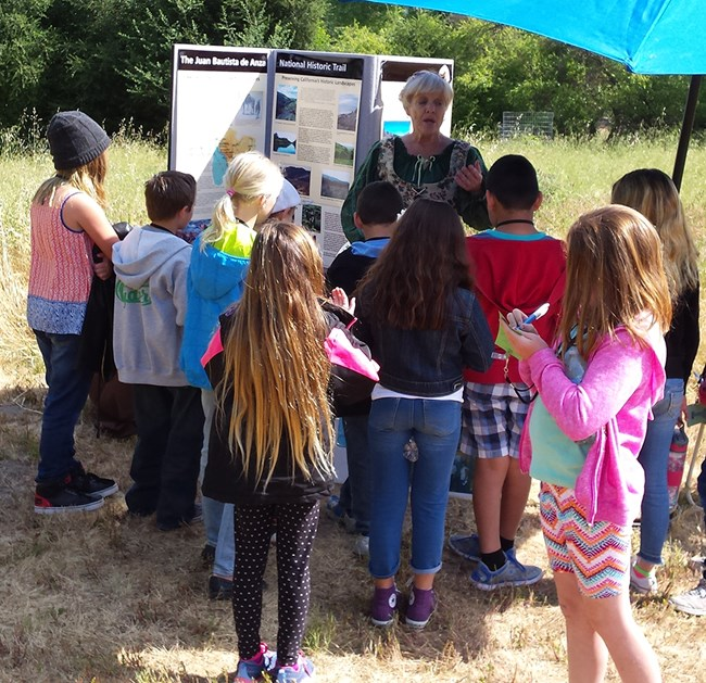 student writes notes at an Anza Trail station