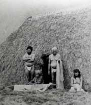 Hawaiian residents at their grass hut in Kalaupapa.