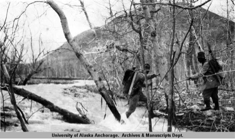 Historic photo of two researchers crossing river.