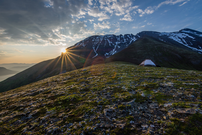 Sunrise over campsite and rugged mountains