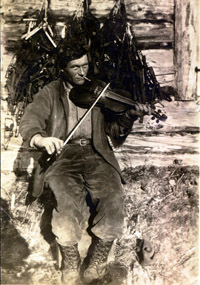 Roy Fure poses with his fiddle outside of his cabin in Bay of Islands.