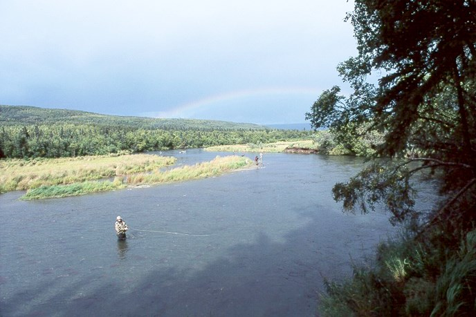 angler stands in river with rainbow on horizon
