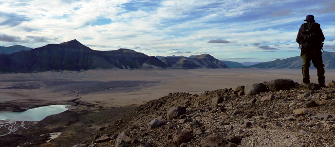 A hiker admires the view of the Valley of Ten Thousand Smokes from the slopes of Mount Mageik.