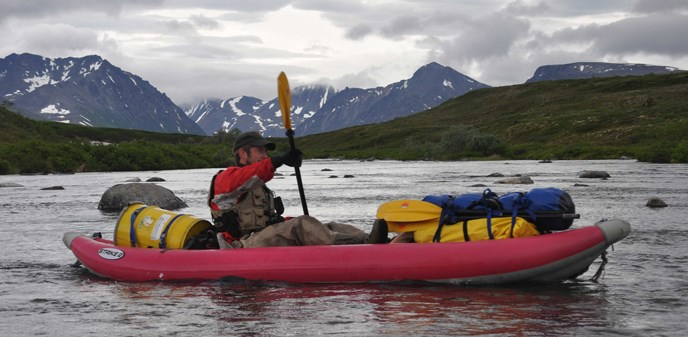A ranger rafts down American Creek