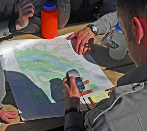 Rangers entering waypoints on a GPS as they study a topographic map