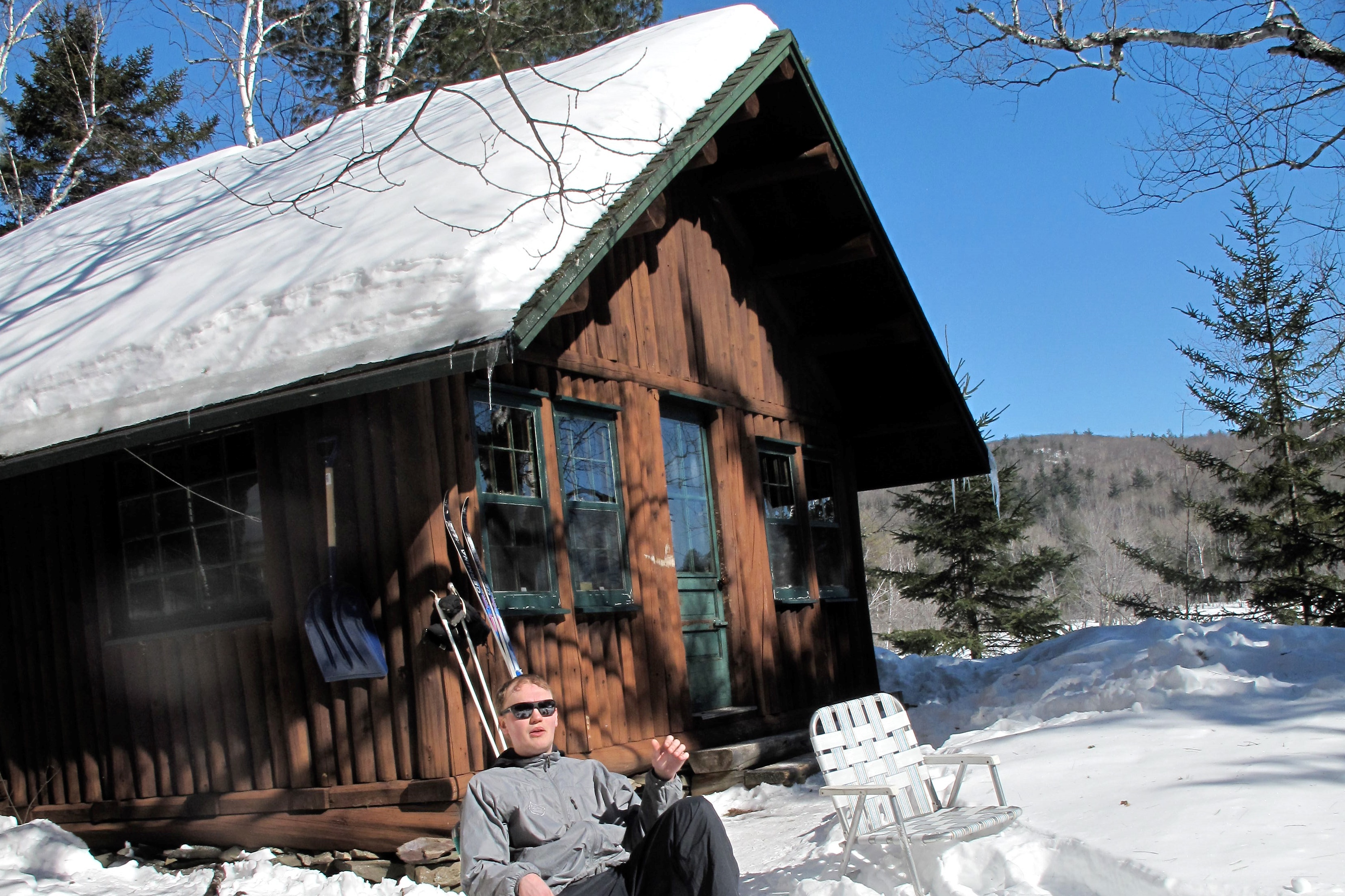 Man sitting in a chair in front of a wooden hut in the snow.