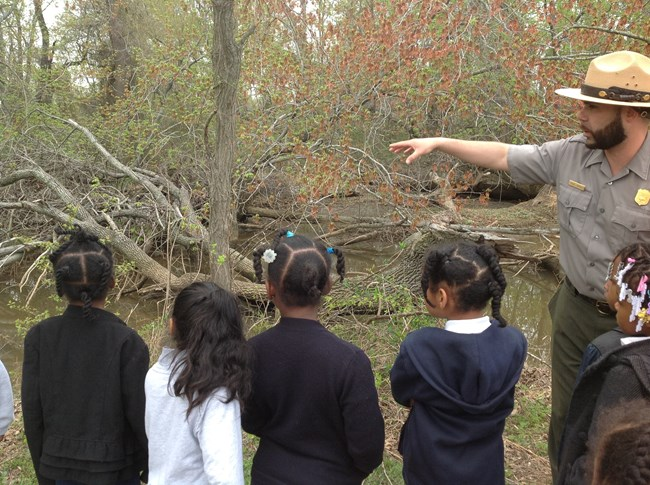 Ranger giving a pond tour to kids