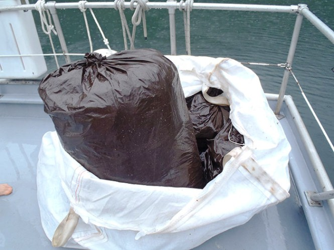 Trash bags of marine debris are piled on the back deck of a boat.