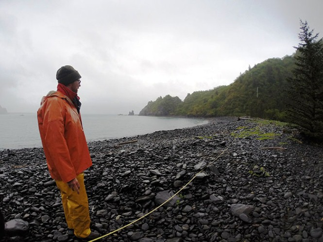 A park tech stands a rocky beach, next to a rope used to mark a line of debris monitoring.