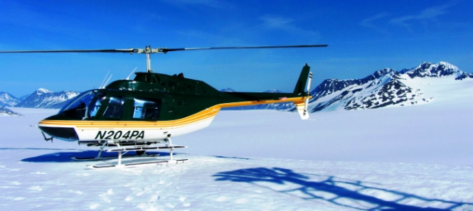 A helicopter sit on the ice field.