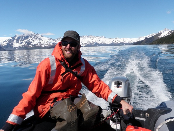 Park researcher drives a small boat through the blue waters of Kenai Fjords National Park.