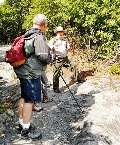 A park ranger talks to visitors while hiking along the park trails.
