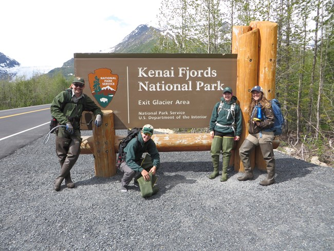 four members of the Invasive Weed team in front of the Kenai Fjords National Park sign