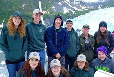 A group of young people pose on a boat in front of a tidewater glacier.
