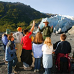 students and ranger stand near a glacier