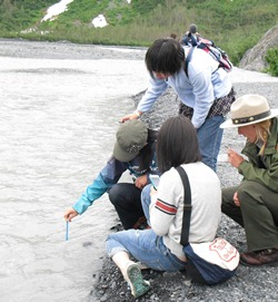 Three students from Obhiro, Japan, stand on the edge of Exit Creek, measuring the temperature of  the water and following the directions of an Education Ranger.