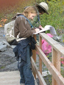 A student stands on a bridge, next to a park ranger, and writes down observations about the plant life of Kenai Fjords.