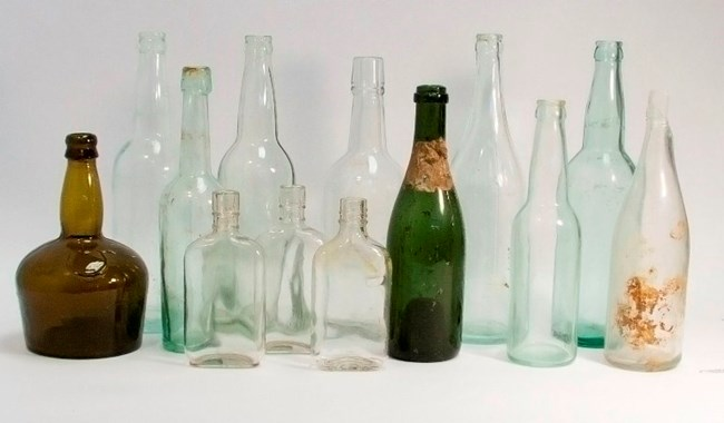A number of old glass bottles sit in front of a plain white background.