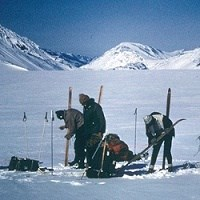 Four skiers from the 1968 crossing of the Harding Icefield prepare their gear.