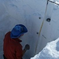 Park scientist measure the year's snow accumulation in an ice pit.