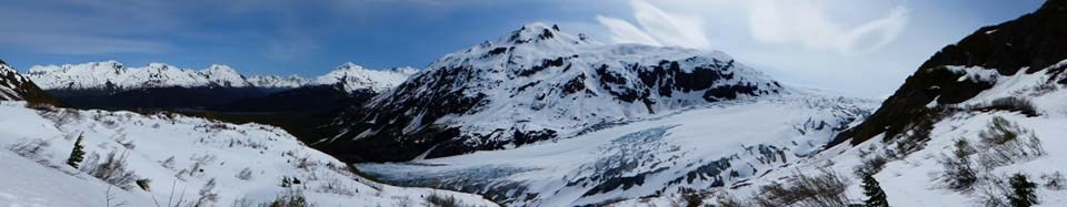 Panorama of Exit Glacier with snow-covered mountains in the background.
