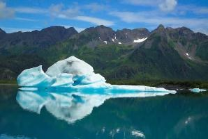 A large iceberg floats in a glacial lagoon with mountains in the background.