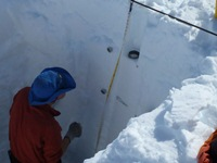 Researchers measuring snow depth and density.