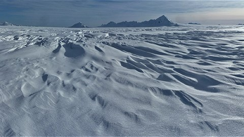 a large area of ice that is covered by snow.  Mountain peaks appear in the distance.
