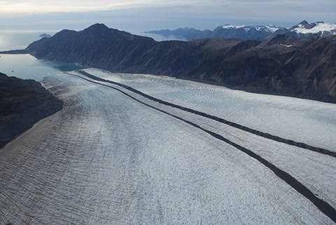 A large white glacier with two dark lines running down the center.  In the upper left of the image the glacier meets the ocean, and in the background are mountains