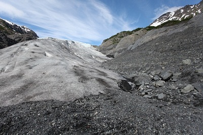 The receding glacier leaves behind bare gravel.