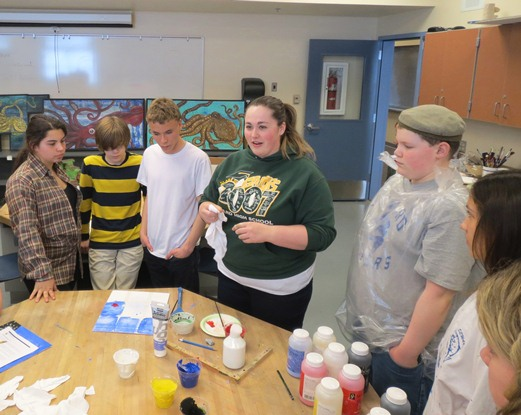 Art students stand around a table while a guest artist teaches them the techniques for their projects.