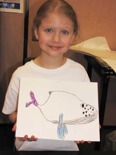 Student holds up marine mammal themed art for National Park Week Art Show