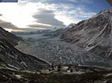 An ice covered lake dammed behind a larger glacier.