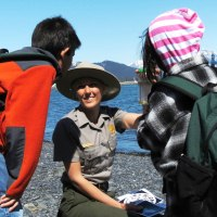 A park ranger holds up a jar of sea water to two children.