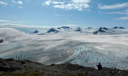 A hiker sits at the end of the Harding Icefield Trail, and looks out over the ice field itself.