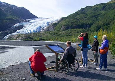 A diverse group of people (including a wheelchair) looking across the outwash plain at a valley glacier in the distance.
