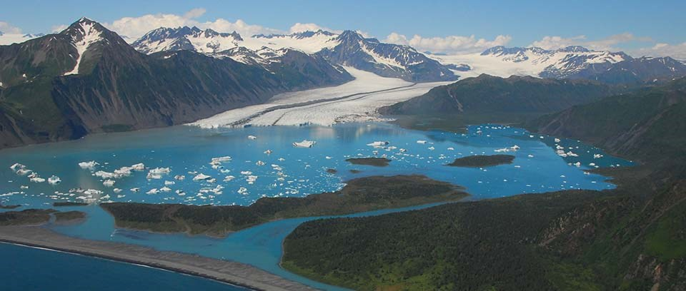 Large lagoon, surrounded by mountains, in front of Bear Glacier with white iceberg floating in the water.