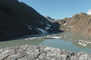 Small lake bordered by steep cliffs in the background and glacial ice in foreground.