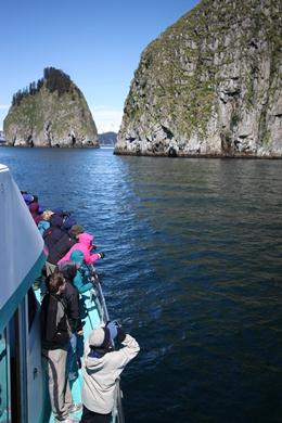 Passengers on a tour boat look out over the side to two rocky islands in the distance.