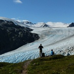 Two hikers stand on a trail, overlooking Exit Glacier as it flows out of the Harding Icefield.